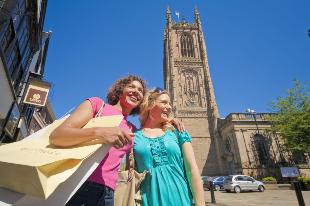 A woman and her daughter with shopping bags in front of Derby Cathedral